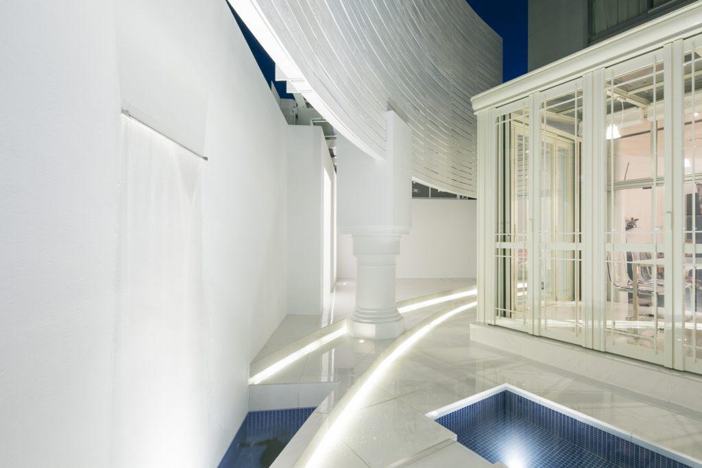 白で統一された中庭がライトアップされガーデンルーム暖蘭物語は神殿の様に見えます