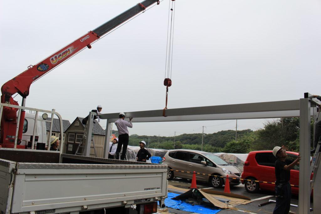 エアロシェードの梁をユニックで吊りながら取る付けています