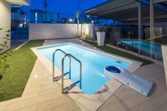 ライトアップされたヤシの木と、ガラスフェンスに映し出されたプールが幻想的な夜のホームリゾート空間を創り出します。