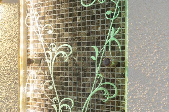 光を当たり浮かび上がるガラス表札の模様